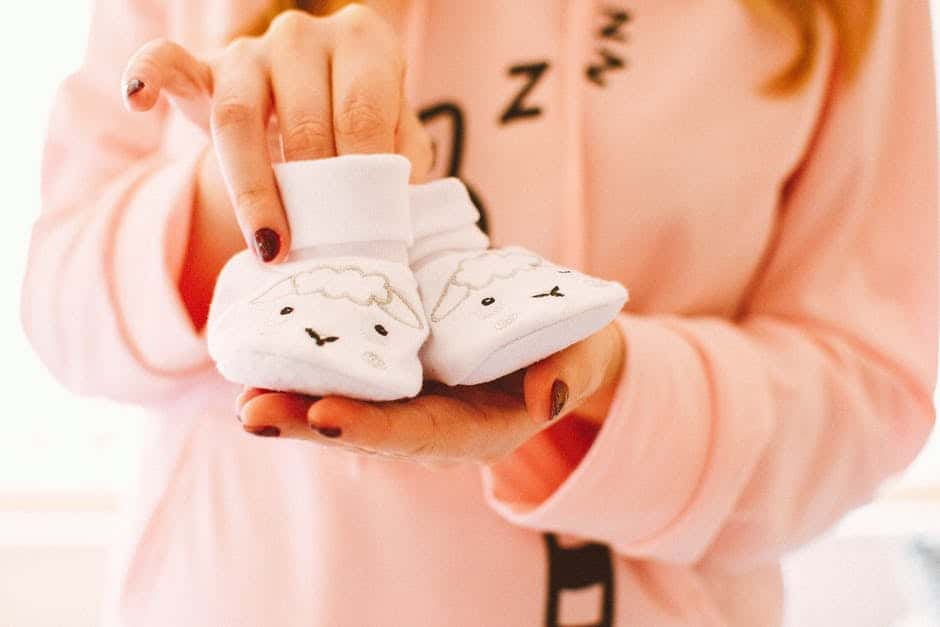 A hand holding a baby shoe