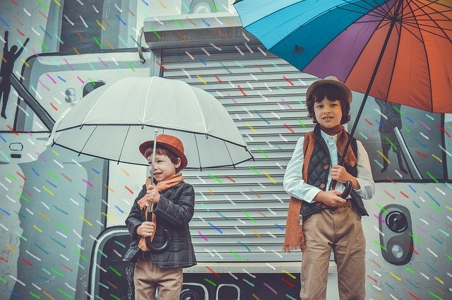 A little boy that is standing in the rain holding an umbrella