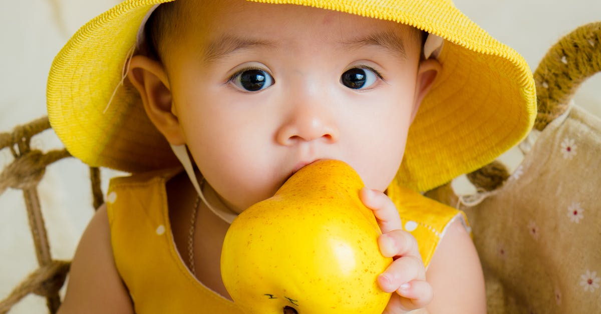 A small child is eating a banana